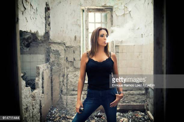 woman exhaling smoke while standing in abandoned home - femme qui fume photos et images de collection