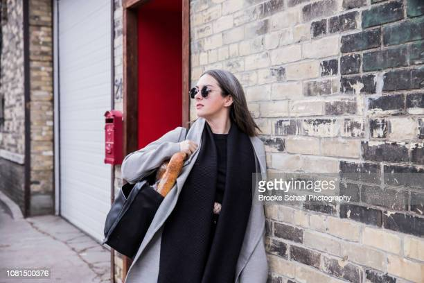 woman exiting a building - graues haar stock-fotos und bilder