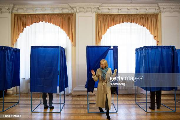 A woman exits a voting booth after marking her ballot at a polling station in Kiev Ukraine on Sunday March 31 2019 Ukrainians will choose between a...