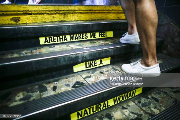A woman exits Franklin Street Subway station while a message for Aretha Franklin is seen on the subway stairs on August 16 2018 in New York New York...