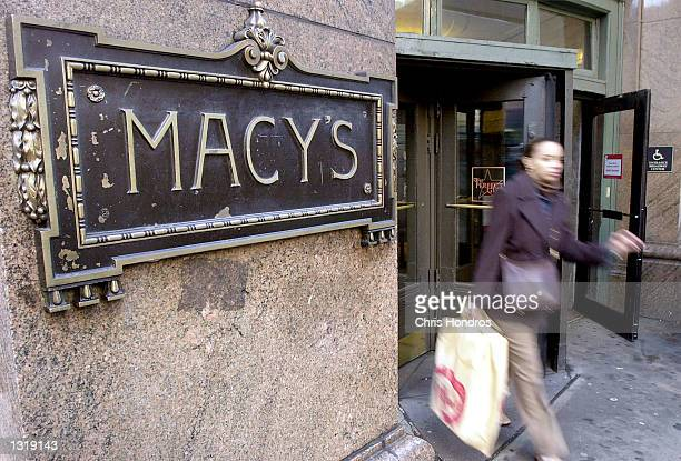 A woman exits Macy''s department store on Sixth Avenue December 14 2000 in New York The holiday shopping season is in full swing bringing thousands...