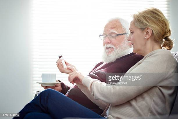 Woman explaining medicine dosage to her father