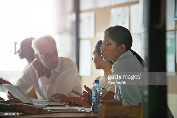 Woman explaining to co-worker, at meeting