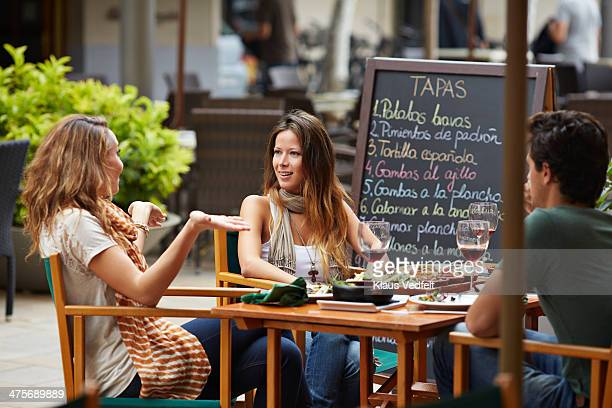 woman explaining to friends at restaurant - klaus vedfelt mallorca stock pictures, royalty-free photos & images