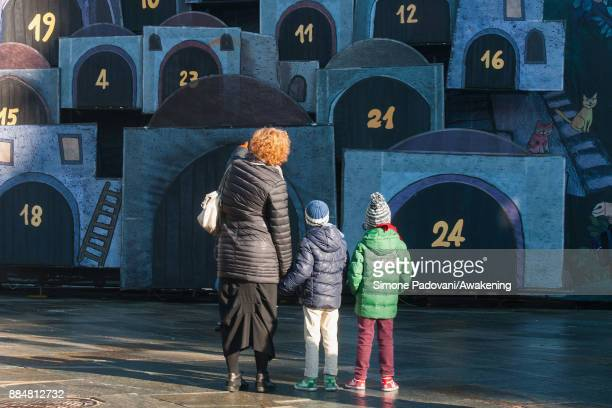 Woman explains the Advent Calendar to two children in Castello square for the Christmas Markets on December 3, 2017 in Turin, Italy.