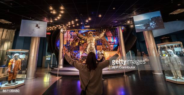 A woman explains to boys how to pose for pictures in front of an artwork depicting a Soviet cosmonaut at the Memorial Museum of Cosmonautics in...