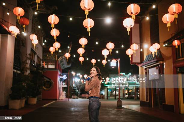 woman explores chinatown in downtown los angeles at night - chinatown stock pictures, royalty-free photos & images