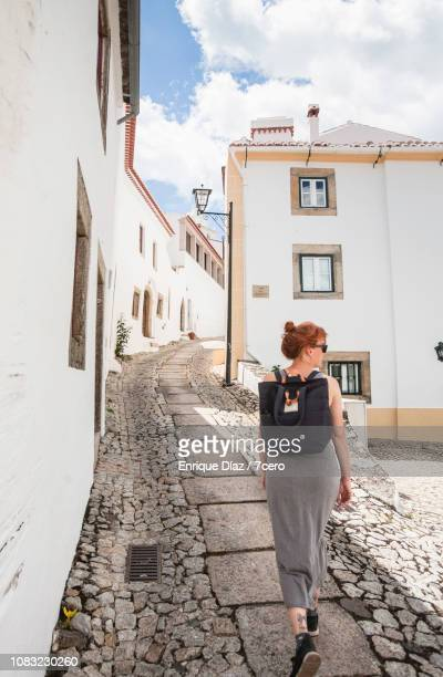 woman explores cobbled steets of marvão old town - long dress stock pictures, royalty-free photos & images