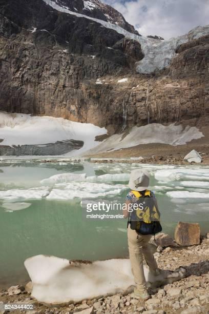 Woman explores hikes Mount Edith Cavell Angel glacier Lake Jasper National Park Alberta Canada