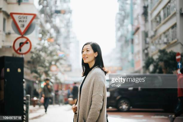 woman exploring in local city street and surrounded by old traditional buildings - reportaje imágenes stock pictures, royalty-free photos & images