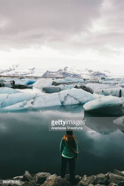 woman exploring jokulsarlon glacier lagoon in iceland - glacier lagoon stock photos and pictures