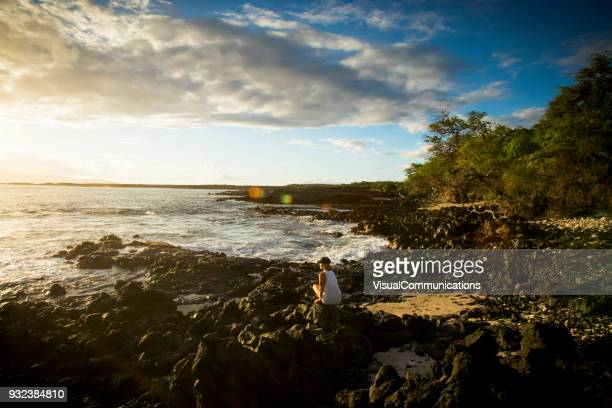 woman exploring on beach in lava plain, maui. - waimea bay hawaii stock photos and pictures