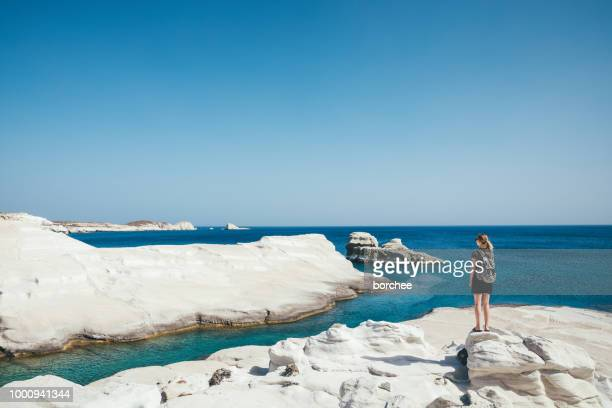 Woman Exploring Sarakiniko Cliffs In Milos