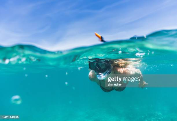 woman exploring the sea while snorkeling in summer day. - underwater stock pictures, royalty-free photos & images