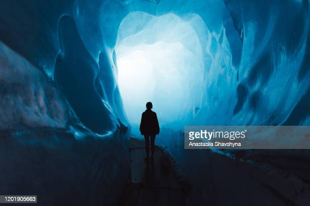 woman exploring the world of a big glacier inside the ice cave in switzerland - tranquil scene stock pictures, royalty-free photos & images