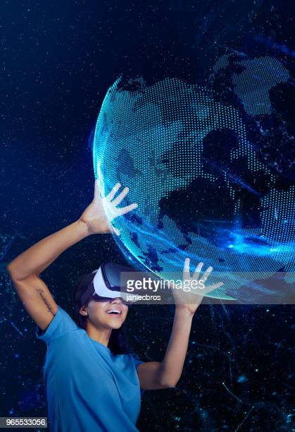 woman exploring virtual reality. holding holographic earth model - human arm stock pictures, royalty-free photos & images