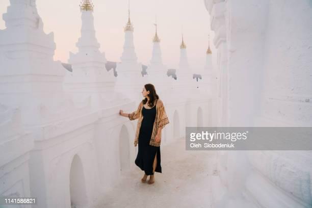 Woman exploring white Hsinbyume Pagoda in Mandalay