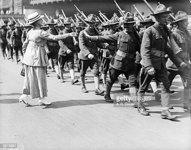 A woman extends a welcoming hand to an American soldier as his troop parades through the streets of London