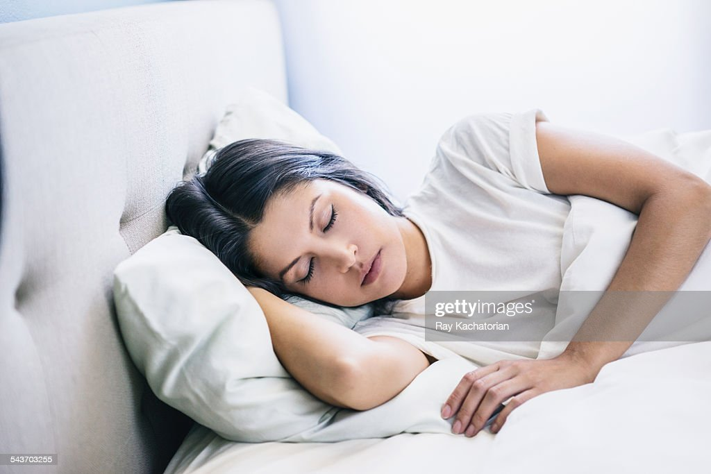 woman eyes closed laying in bed : Stock Photo