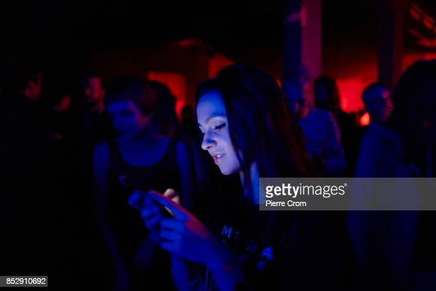 A woman eyes her smartphone during an underground party in a former factory on September 24 2017 in Minsk Belarus