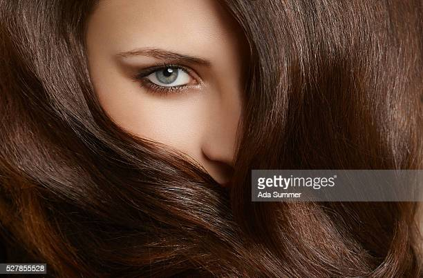 woman face covered with brown wavy hair