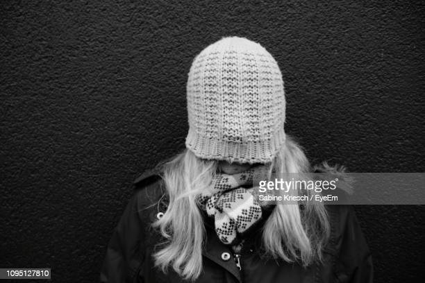 woman face covered with knit hat while standing against wall - sabine kriesch stock-fotos und bilder