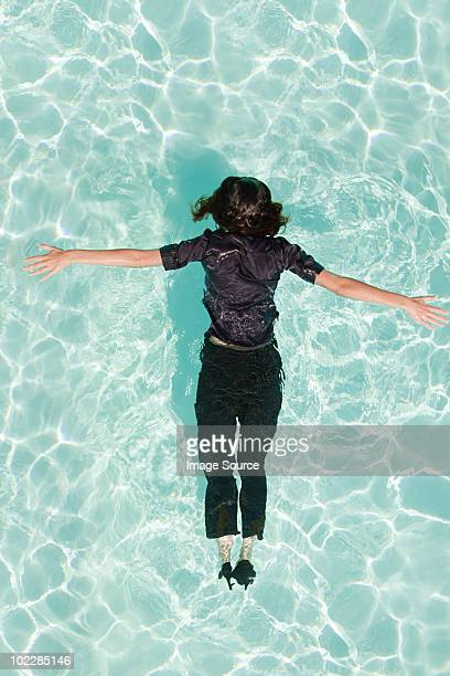 woman face down in swimming pool - down blouse stock photos and pictures