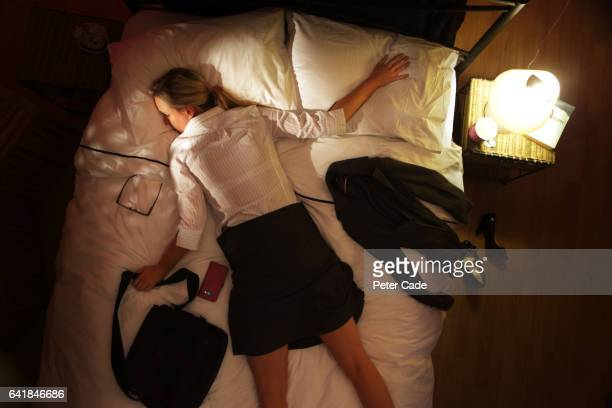 woman face down on bed wearing suit - exhaustion stock pictures, royalty-free photos & images