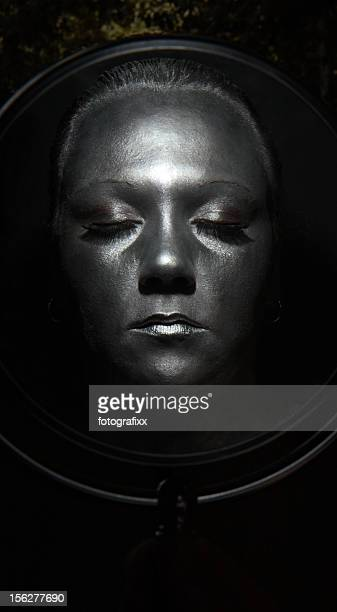 Woman Face Painted Silver in Mirror