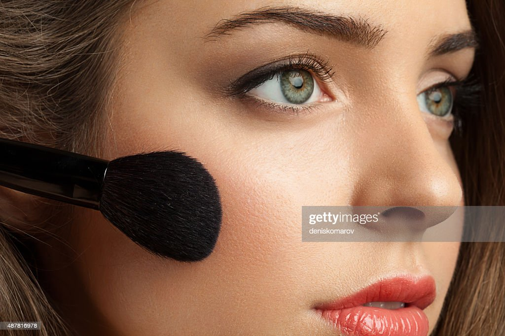 Woman face powders, and apply blush to the cheekbones : Stock Photo