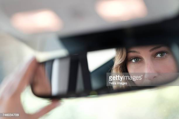 Woman face reflected in rearview mirror