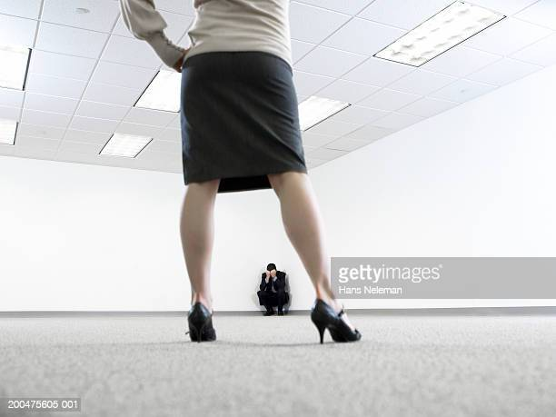Woman facing man crouching in corner of room, rear view of woman