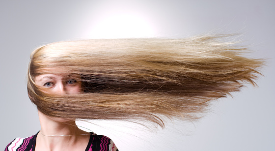 Woman facing straight ahead with hair being blown aside 157402158