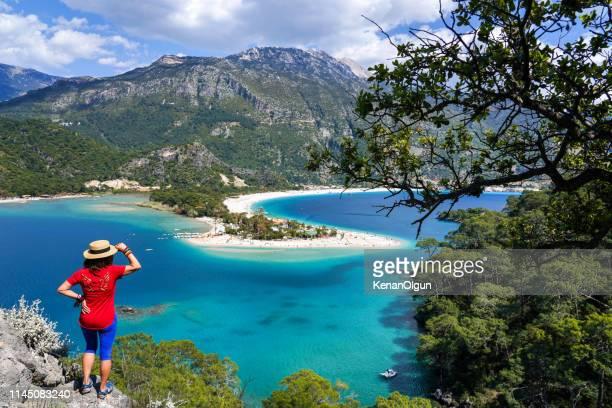 woman facing the beach. ölüdeniz from fethiye, turkey. - aegean turkey stock pictures, royalty-free photos & images