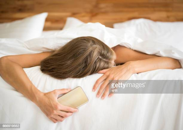 Woman falling asleep with smart phone in her hand