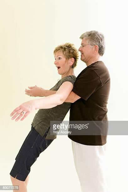 woman falling back into mans arms - reggere foto e immagini stock
