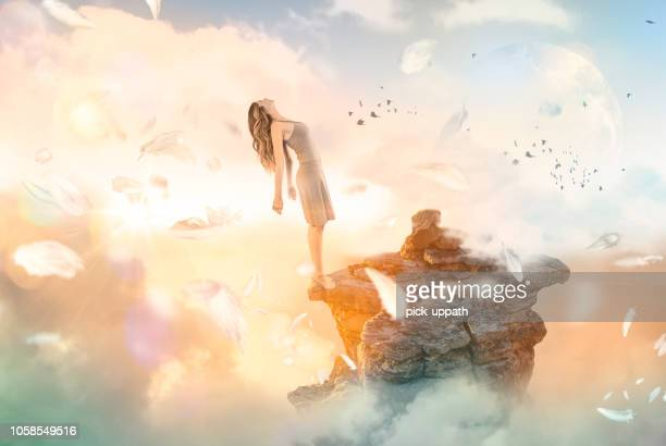 woman falling backwards off cliff into heaven - elysium stock pictures, royalty-free photos & images