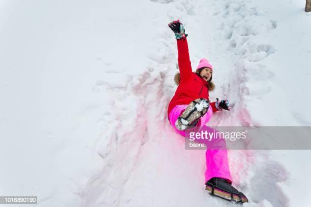 femme tombant sur la route de neige - lying down photos et images de collection