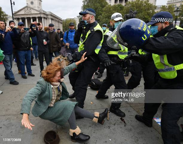TOPSHOT A woman falls as police move in to disperse protesters in Trafalgar Square in London on September 26 at a 'We Do Not Consent' mass rally...
