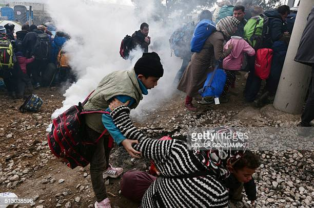 A woman falls as refugees with their children run away after Macedonian police used tear gas to dispearse refugees trying to break the gate to enter...