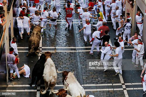A woman falls as revellers run with Fuente Ymbro's fighting bulls entering Estafeta Street during the second day of the San Fermin Running of the...
