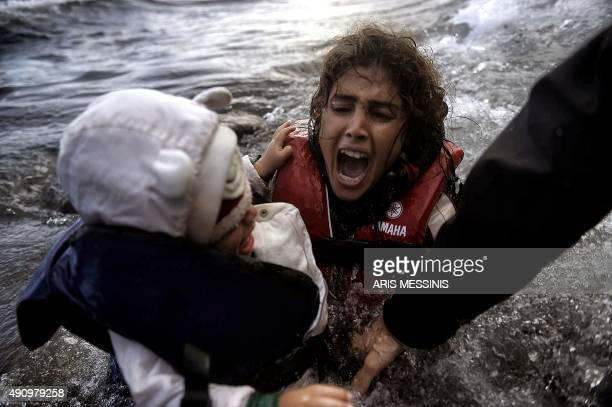 A woman falls into the water with her child as they disembark off a dinghi as refugees and migrants arrive at the Greek island of Lesbos after...