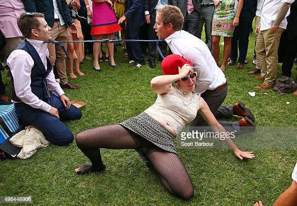 A woman falls over after attempting to bend backwards between two racegoers who have their ties tied together as racegoers play a game of Limbo...