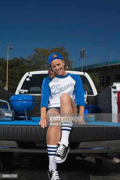 woman fan sitting on tailgate - vehicle grille stock pictures, royalty-free photos & images