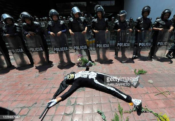 A woman fancy dressed as a skeleton performs in front of riot police members during a demonstration against the lack of safety on the streets on June...