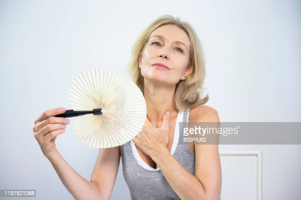 woman fanning herself to relieve the symptoms of a hot flush. - menopause stock photos and pictures