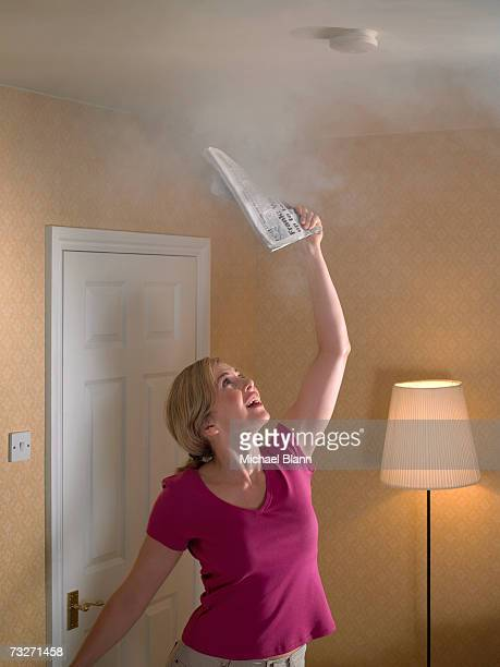 Woman fanning smoke smoke detector with newspaper