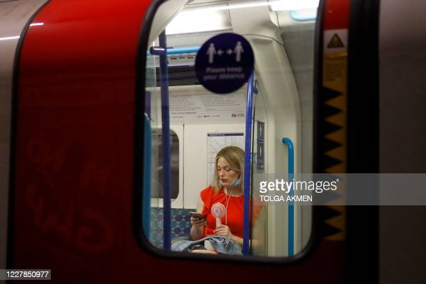 Woman fans herself with an electric fan as she looks at her smartphone on the tube in central London as the temperature rises in the capital on July...