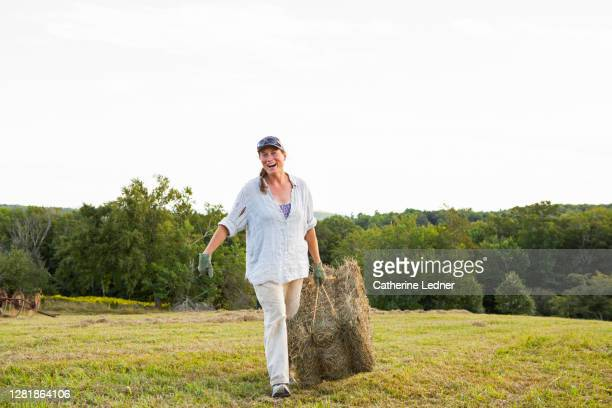 woman farm owner and worker caring just baled hay through her field. - catherine ledner stock pictures, royalty-free photos & images
