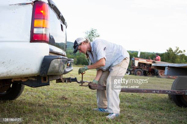 woman farm owner hooking up her truck to a trailer to haul hay from freshly shorn field in rural maine - catherine ledner stock pictures, royalty-free photos & images